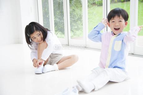 床に座って笑う男の子と女の子の写真素材 [FYI02966370]