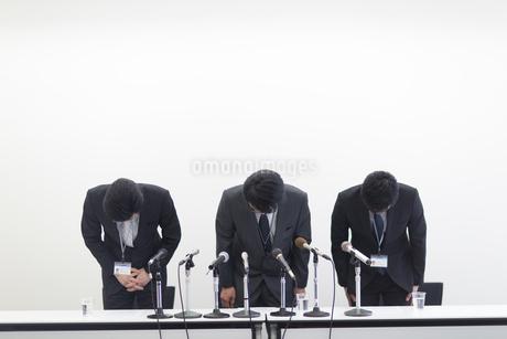 謝罪会見で頭を下げるビジネス男性3人の写真素材 [FYI02966371]