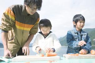 湖畔でニンジンを切る成人男性と2人の男の子の写真素材 [FYI02966374]