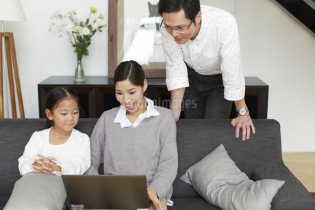 ソファーでノートパソコンを見る家族の写真素材 [FYI02966378]