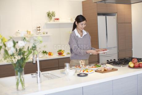 テーブルの上で花瓶の花を見る主婦の写真素材 [FYI02966379]