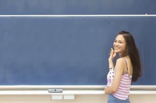 黒板の前で笑顔で振り向く女子学生の写真素材 [FYI02966382]