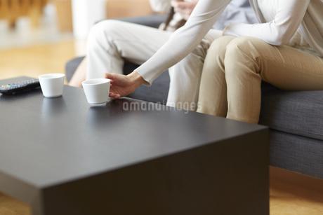 コーヒーカップを置く女性の手の写真素材 [FYI02966383]