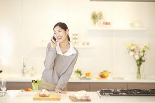 スマートフォンで話しながら笑う女性の写真素材 [FYI02966387]