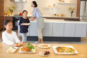 テーブルに食事を用意する親子の写真素材 [FYI02966388]