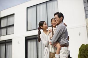 家の前に立つ3人家族の写真素材 [FYI02966399]