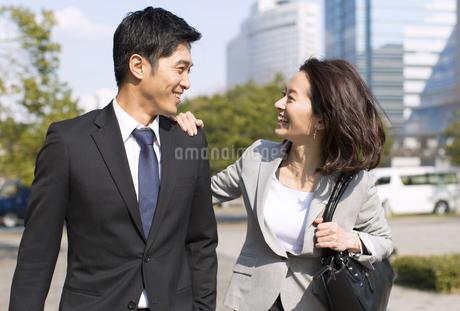 肩に手をかけて挨拶をするビジネス男女の写真素材 [FYI02966401]