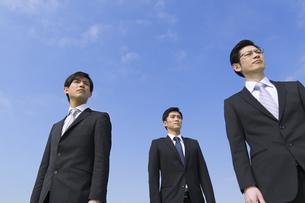 青空を背景に立つ3人のビジネス男性の写真素材 [FYI02966404]