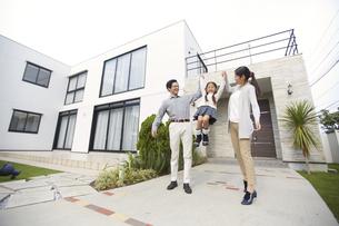 家の前で両親に高く上げてもらい喜ぶ女の子の写真素材 [FYI02966408]
