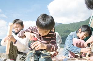 湖畔で木の工作をする4人の男の子の写真素材 [FYI02966409]