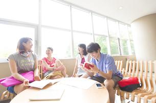 円形のテーブルを囲んで笑い合う学生たちの写真素材 [FYI02966412]