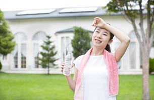 ペットボトルを持って額に腕をあてる女性の写真素材 [FYI02966417]