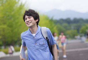 微笑みながらキャンパスを歩く男子学生の写真素材 [FYI02966420]