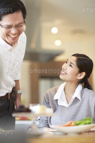 料理を前に笑顔で会話する男女の写真素材 [FYI02966422]
