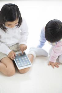 床に座ってタブレットPCを見る2人の子供の写真素材 [FYI02966423]