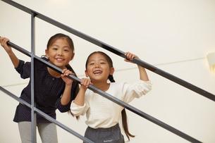 手すりを掴んで笑顔の姉妹の写真素材 [FYI02966425]