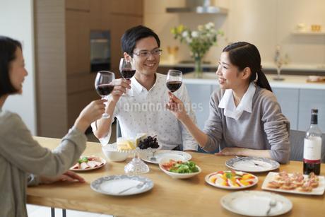 ホームパーティでワインを手に会話する男女三人の写真素材 [FYI02966431]
