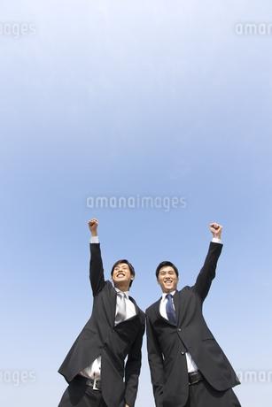 青空を背景にこぶしを上げるビジネス男性2人の写真素材 [FYI02966433]