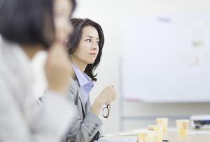 眼鏡を持って話を聞くビジネス女性の写真素材 [FYI02966435]