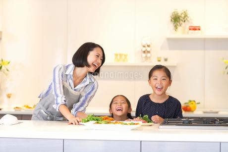 キッチンで料理を前に笑う親子の写真素材 [FYI02966436]