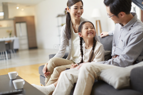 ソファーで会話する3人家族の写真素材 [FYI02966438]