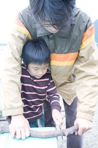 屋外で木の工作をする父と息子の写真素材 [FYI02966439]