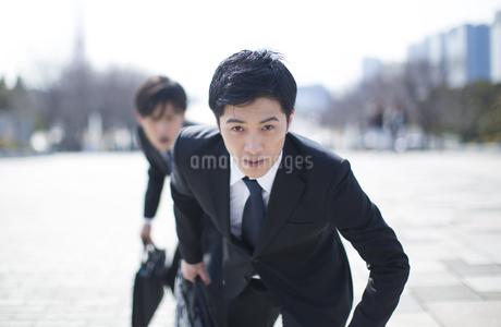 駆けだすポーズをとるビジネス男性2人の写真素材 [FYI02966440]