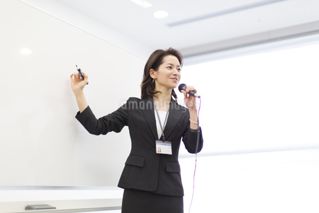 マイクを手に講義するビジネス女性の写真素材 [FYI02966444]