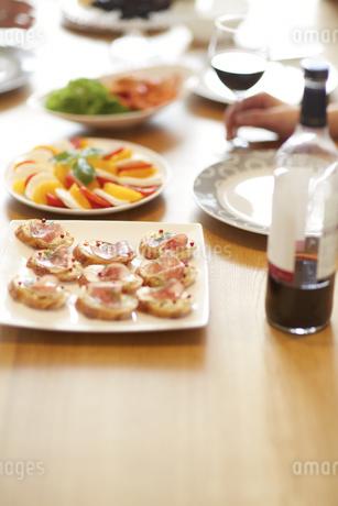 オードブルとワインを持つ手の写真素材 [FYI02966445]