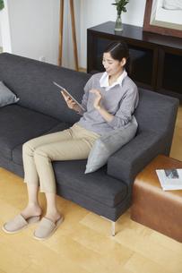 ソファーでスマートデバイスを見て微笑む女性の写真素材 [FYI02966446]