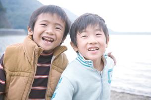 湖畔で肩を組んで笑う2人の男の子の写真素材 [FYI02966447]