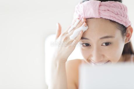 鏡の前で頬にコットンをあてスキンケアをする女性の写真素材 [FYI02966448]