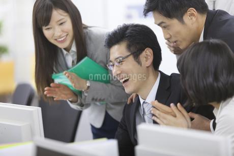 パソコンを見て喜ぶビジネス男女の写真素材 [FYI02966451]