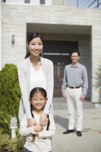 母と子が手前で家の前に立つ夫婦の写真素材 [FYI02966457]
