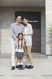 家の前に立つ3人家族の写真素材 [FYI02966458]