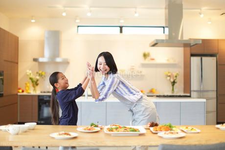 食事を置いたテーブルの前でハイタッチする親子の写真素材 [FYI02966459]