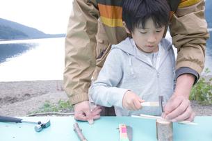 湖畔で木の工作を教わる男の子の写真素材 [FYI02966465]