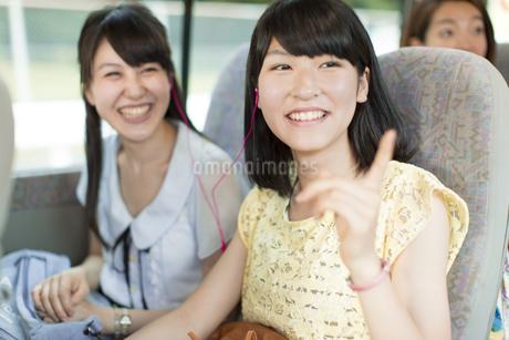 バスの車中でイヤホンをして景色を見る2人の女性の写真素材 [FYI02966467]