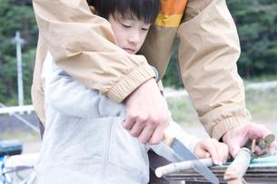 屋外で木の工作を教わる男の子の写真素材 [FYI02966472]