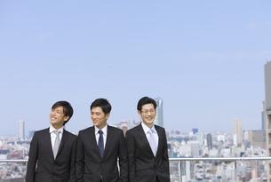 青空とビルを背景に笑う3人のビジネス男性の写真素材 [FYI02966474]