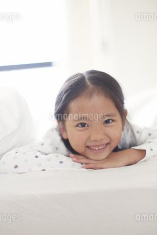 うつ伏せで微笑むパジャマ姿の女の子のスナップの写真素材 [FYI02966477]