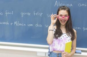 黒板の前で眼鏡を下して笑う女子学生のポートレートの写真素材 [FYI02966478]