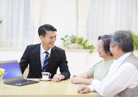 説明する訪問営業の男性と話を聞くシニア夫婦の写真素材 [FYI02966485]