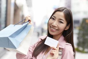 買い物バッグとカードを見せて微笑む女性の写真素材 [FYI02966487]