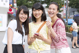街中で微笑む3人の女性のポートレートの写真素材 [FYI02966491]