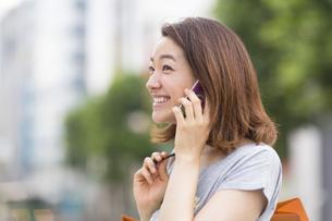 街中でスマートフォンで話す若い女性の写真素材 [FYI02966492]