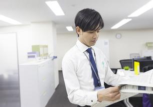 オフィスで新聞を読むビジネス男性の写真素材 [FYI02966497]