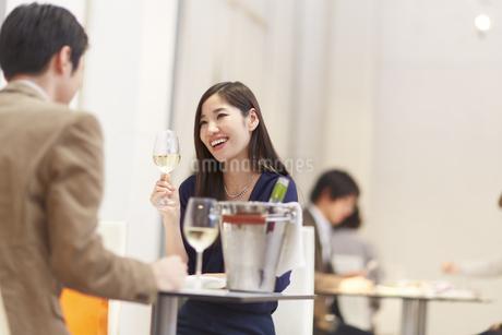 レストランでワインを手に笑い合うカップルの写真素材 [FYI02966499]