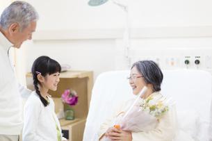 お見舞いにきて花束を渡す女の子の写真素材 [FYI02966505]