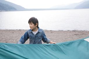 湖畔でテントを畳むのを手伝う男の子の写真素材 [FYI02966506]